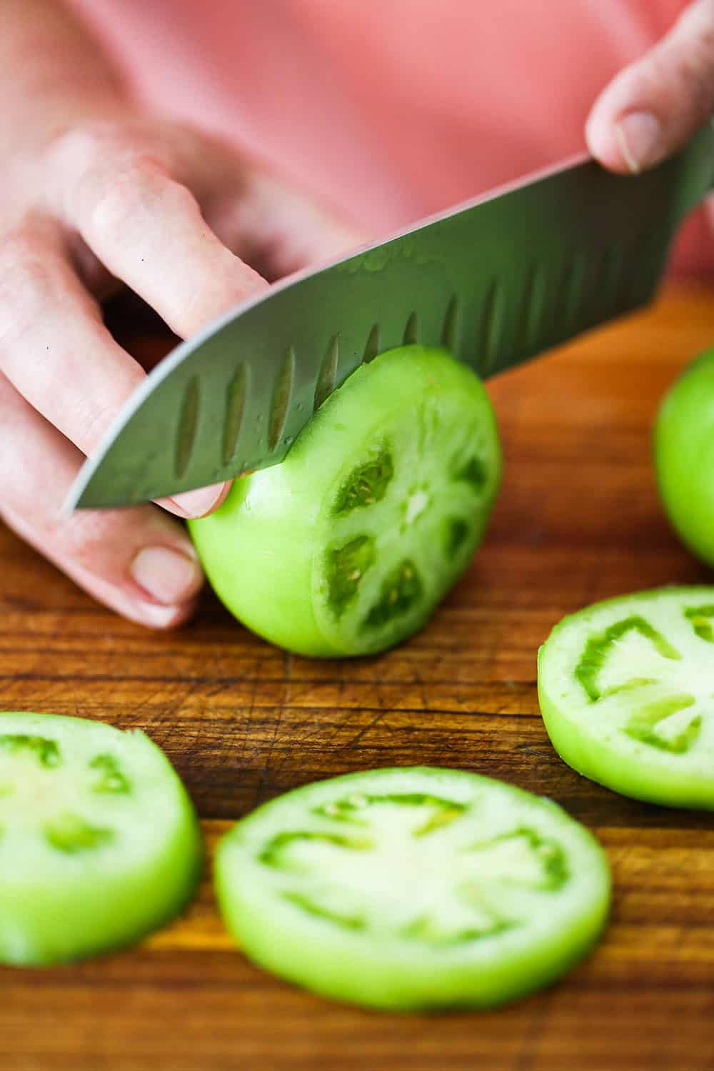 A person using a chef's knife to slice a green tomato on a cutting board with slices scattered around.