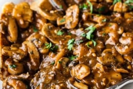 An oval white platter filled with chicken marsala with a serving spoon off to the side.