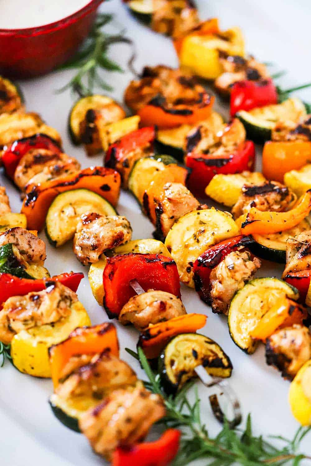 A row of 5 chicken kabobs on a white oval platter garnish with fresh rosemary sprigs and a bowl of white sauce.