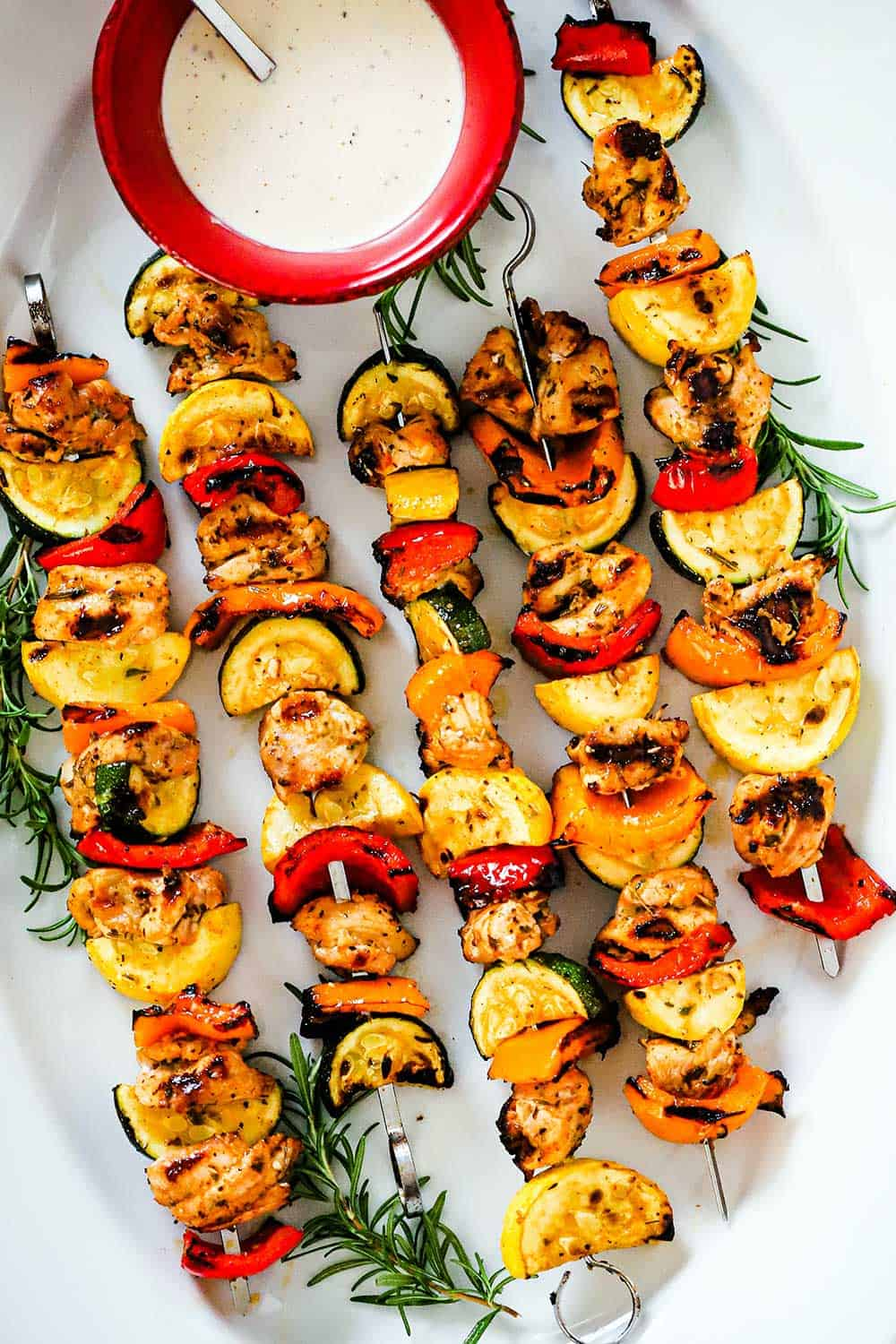 A large white oval platter filled with grilled chicken and vegetable kabobs with a red bowl filled with white BBQ sauce nestled in.