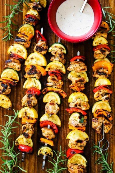 Five grilled chicken kabobs on metal skewers lined with vegetables and a red bowl of white BBQ sauce nearby.