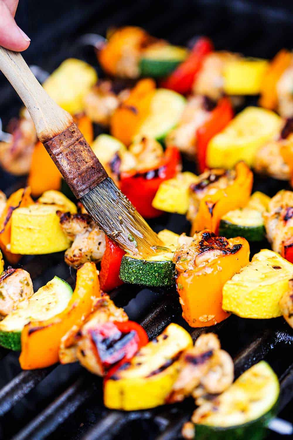 A person brushing marinade onto skewers on a grill that contain pieces of uncooked chicken as well as bell peppers, squash, and zucchini pieces.
