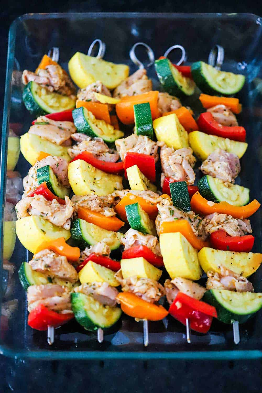 A 9x13-inch glass baking dish filled with 5 chicken and vegetable kabobs.