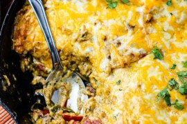 King Ranch casserole in a large cast iron skillet with a spoon in it all next to festive napkins.