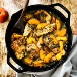 A large black cast-iron skillet filled with pan-fried pork cutlets and peaches in a savory sauce all next to several whole peaches.