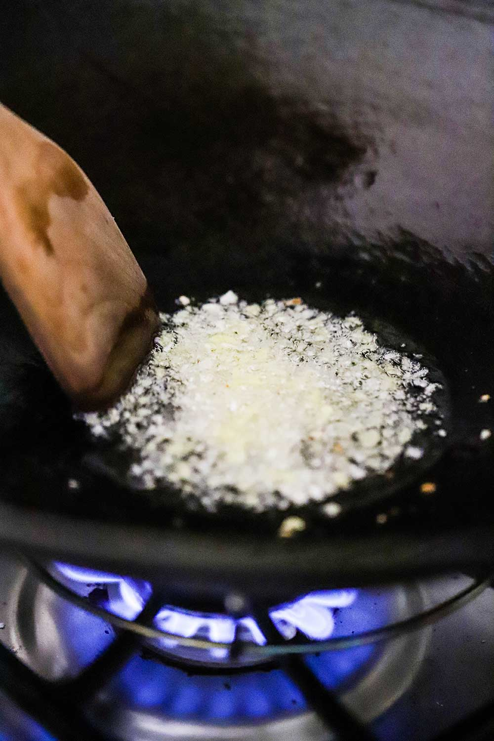 A wok on a gas-burning stove with hot oil and simmering minced garlic and ginger in it.