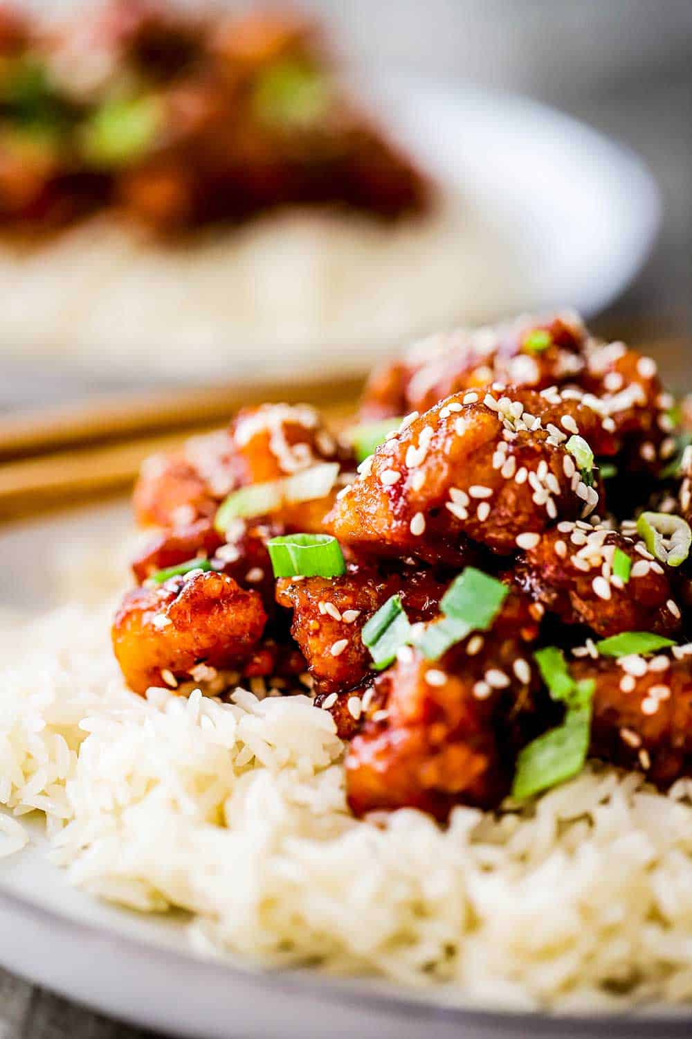 A close-up view of plate filled with sesame chicken on top of a bed of rice.