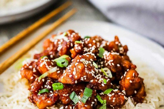 A dinner plate filled with a bed of white rice with sesame chicken on top of it and a pair of chop sticks nearby.