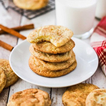 A stack of snickerdoodle cookies on a small white plate surrounded by other cookies and a glass of milk.