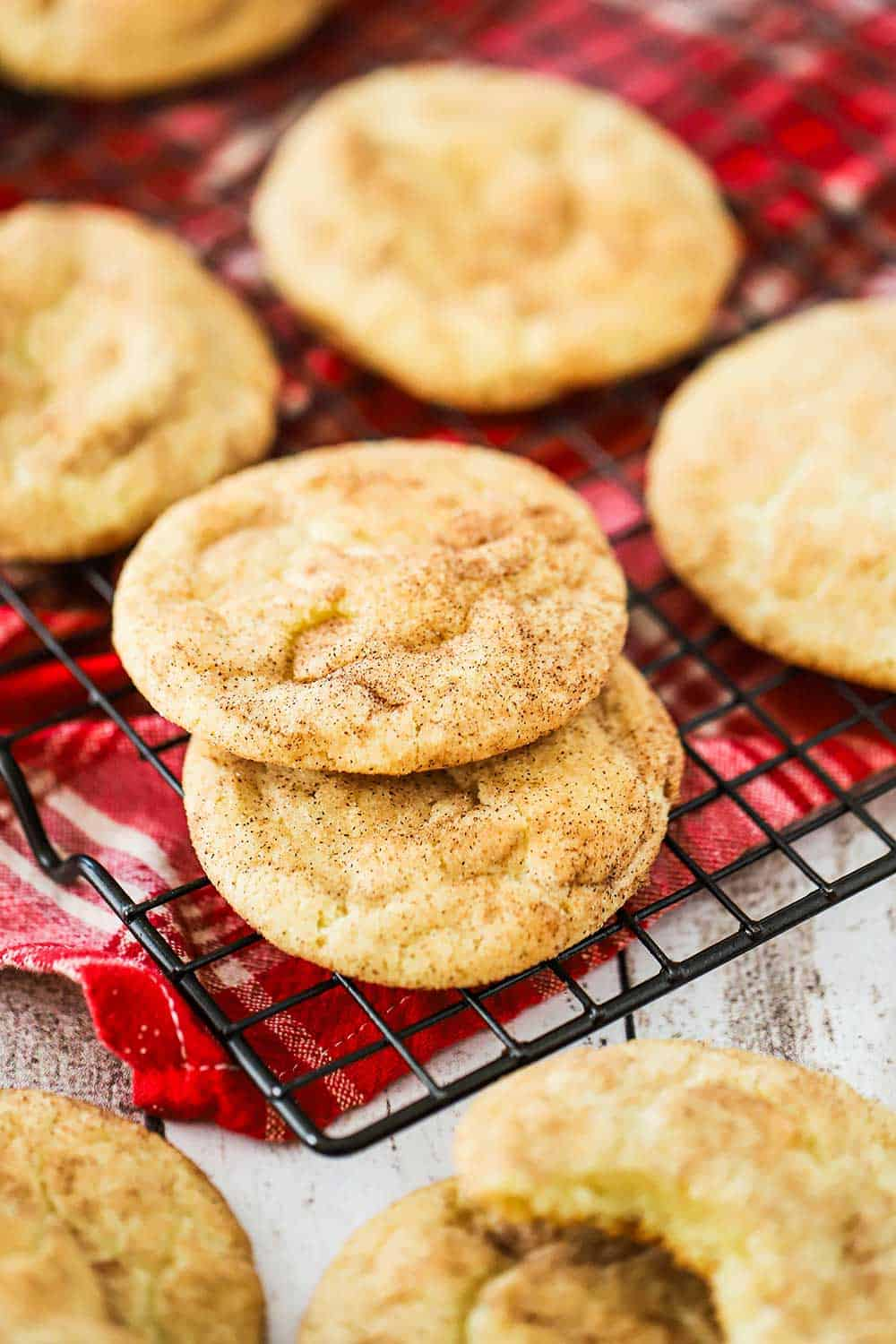 A baking rack topped with snickerdoodle cookies all on top of a red-checkered napkin.