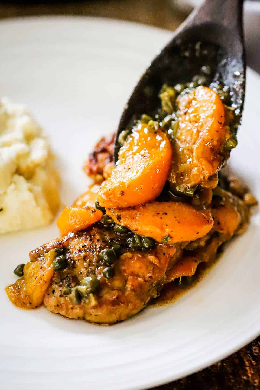 A wooden spoon transferring sautéed peaches and capers onto pan-fried pork cutlets on a white dinner plate.