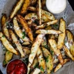A pile of garlic parmesan steak fries sitting on a board lined with parchment paper with a small bowl of ketchup on one side and a bowl of aioli on the other side.