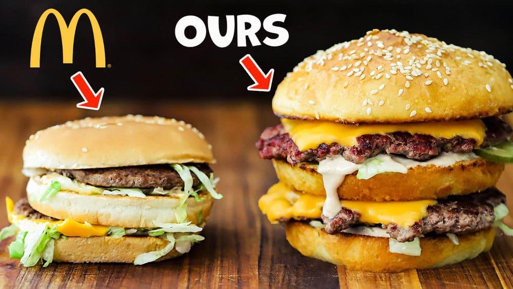A McDonald's Big Mac sitting next to a homemade Big Mac both on a wooden cutting board.