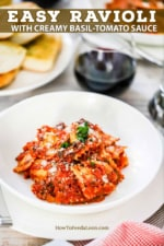 An individual white pasta bowl filled with ravioli and a tomato sauce next to a stemless wine glass filled with red wine and a plate of garlic bread nearby.