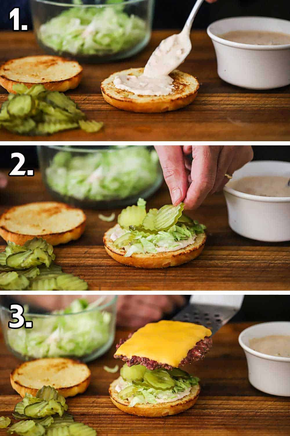 A person spooning Russian dressing onto a bottom hamburger bun and then that person placing lettuce and pickles on it and then a hamburger patty with cheese on top.