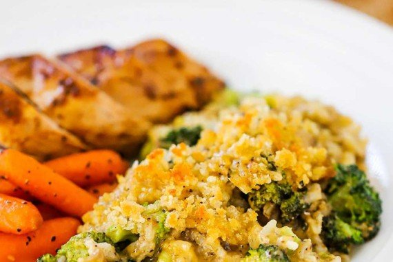 A white dinner plate filled with a large helping of broccoli casserole next to carrots nubs and a sliced grilled breast of chicken.