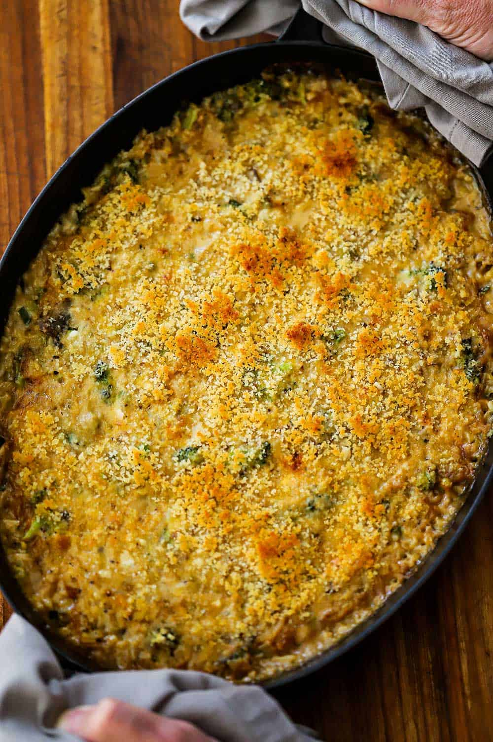 A large oval baking dish filled with broccoli casserole with cheddar and rice fresh out of the oven.