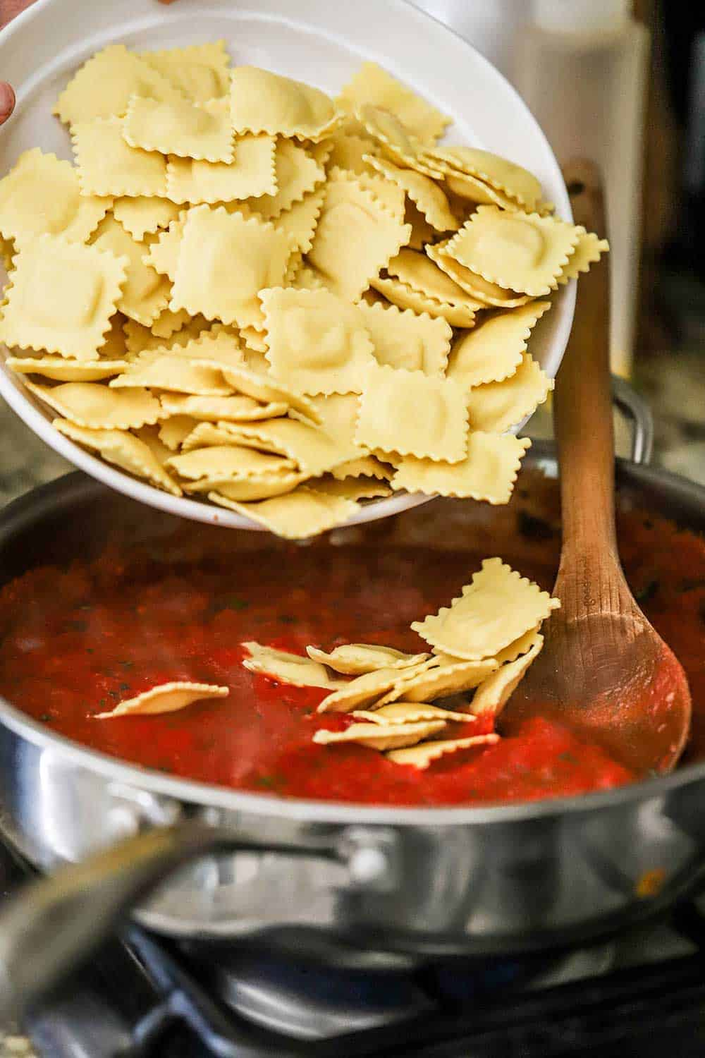 A person dumping a white bowl filled with fresh ravioli into a large skillet filled with a tomato sauce.
