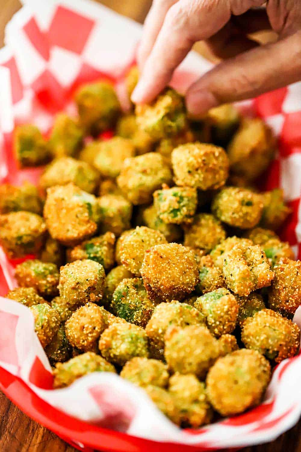 A person reaching into a basket lined with red checkered paper and filled with fried okra.