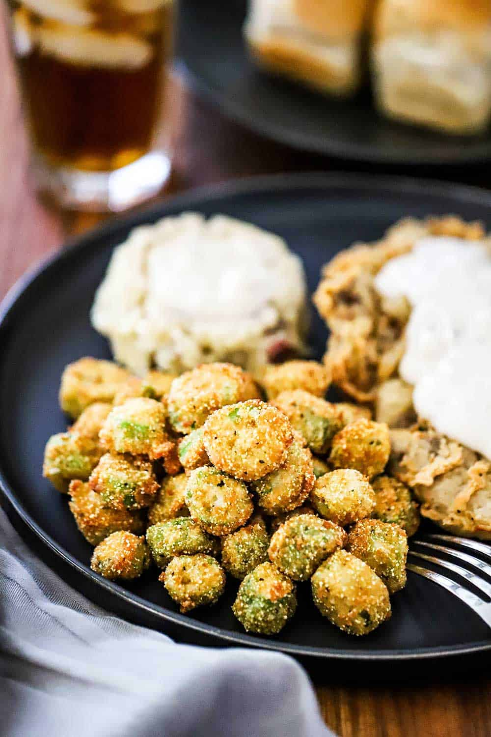 A blue dinner plate willed with chicken fried steak, mashed potatoes, both topped with gravy, all next to a pile of fried okra.