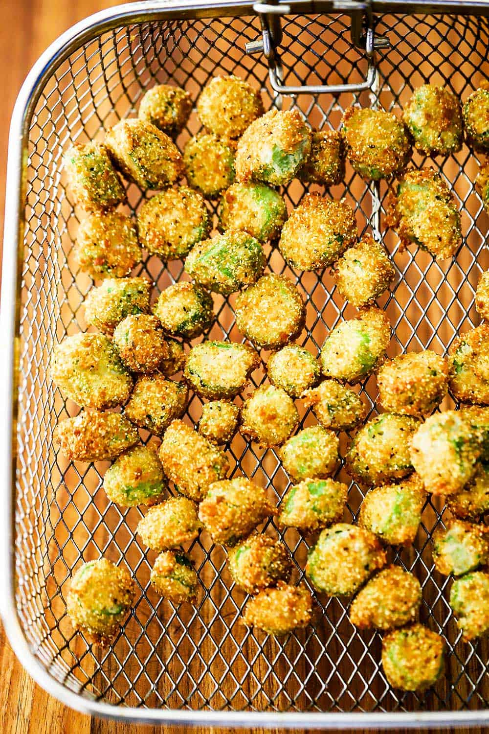 A fryer basket will with fried okra all over a wooden cutting board.