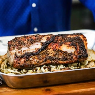 A person holding a large steel roasting pan filled with a roasted pork loin sitting on top of roasted apples and fennel.