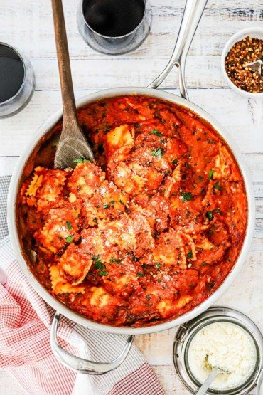 A large silver skillet filled with easy ravioli with creamy basil-tomato sauce with a wooden spoon stuck in it.