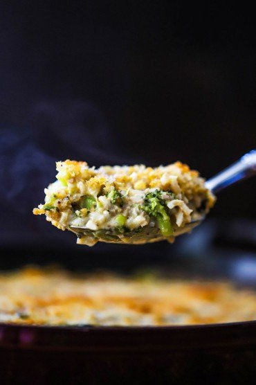 A large silver spoon lifting up a steaming helping of broccoli casserole over a dish of the same.