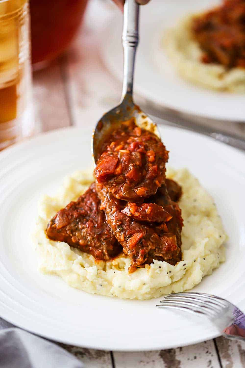 A person using a large silver spoon to pour Swiss steak sauce over two piece of meat sitting on a bed of mashed potatoes on a white dinner plate.