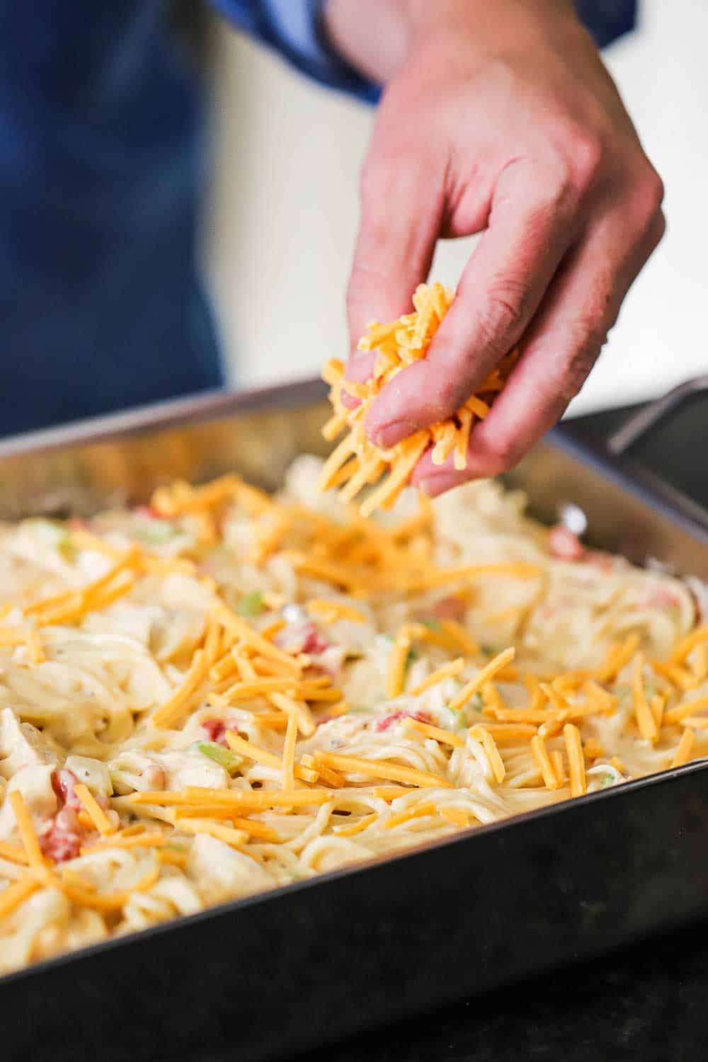 A hand sprinkling shredded cheddar over the top of an uncooked pan of chicken spaghetti.