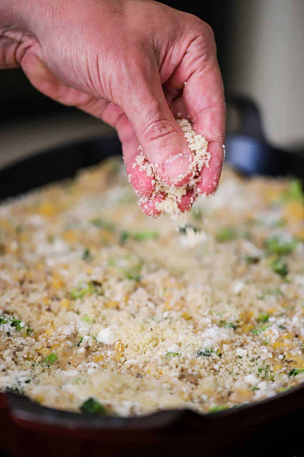 A person sprinkling bread crumbs over the top of an uncooked broccoli casserole in a large oval baking dish.