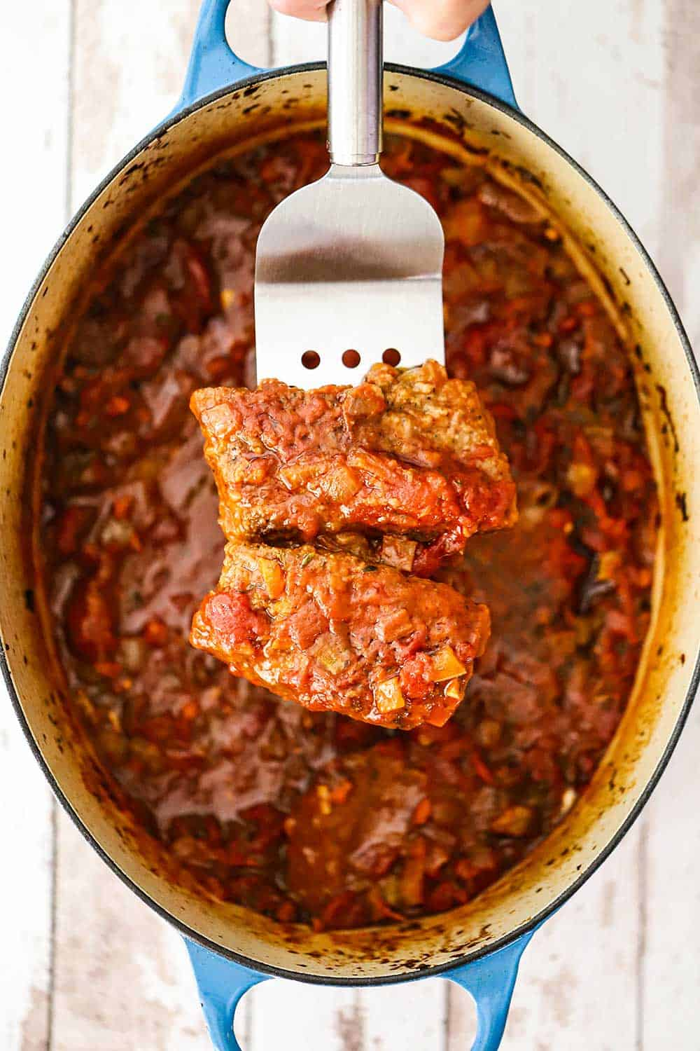 A metal spatula holding up two steak fillets covered in a red tomato sauce directly over an oval Dutch oven filled with Swiss steak.