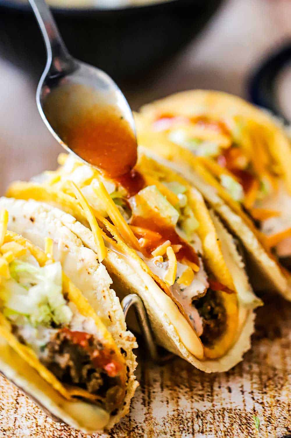 A spoon pouring taco sauce over the top of three stuffed tacos sitting on a metal taco holder.