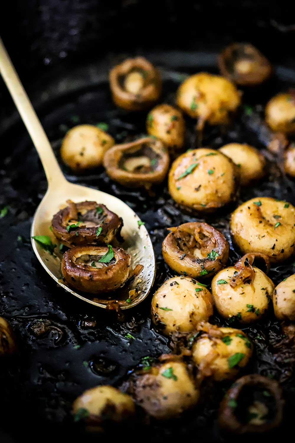 A black cast-iron skillet filled with sautéed mushrooms with a gold spoon holding a couple of the mushrooms.