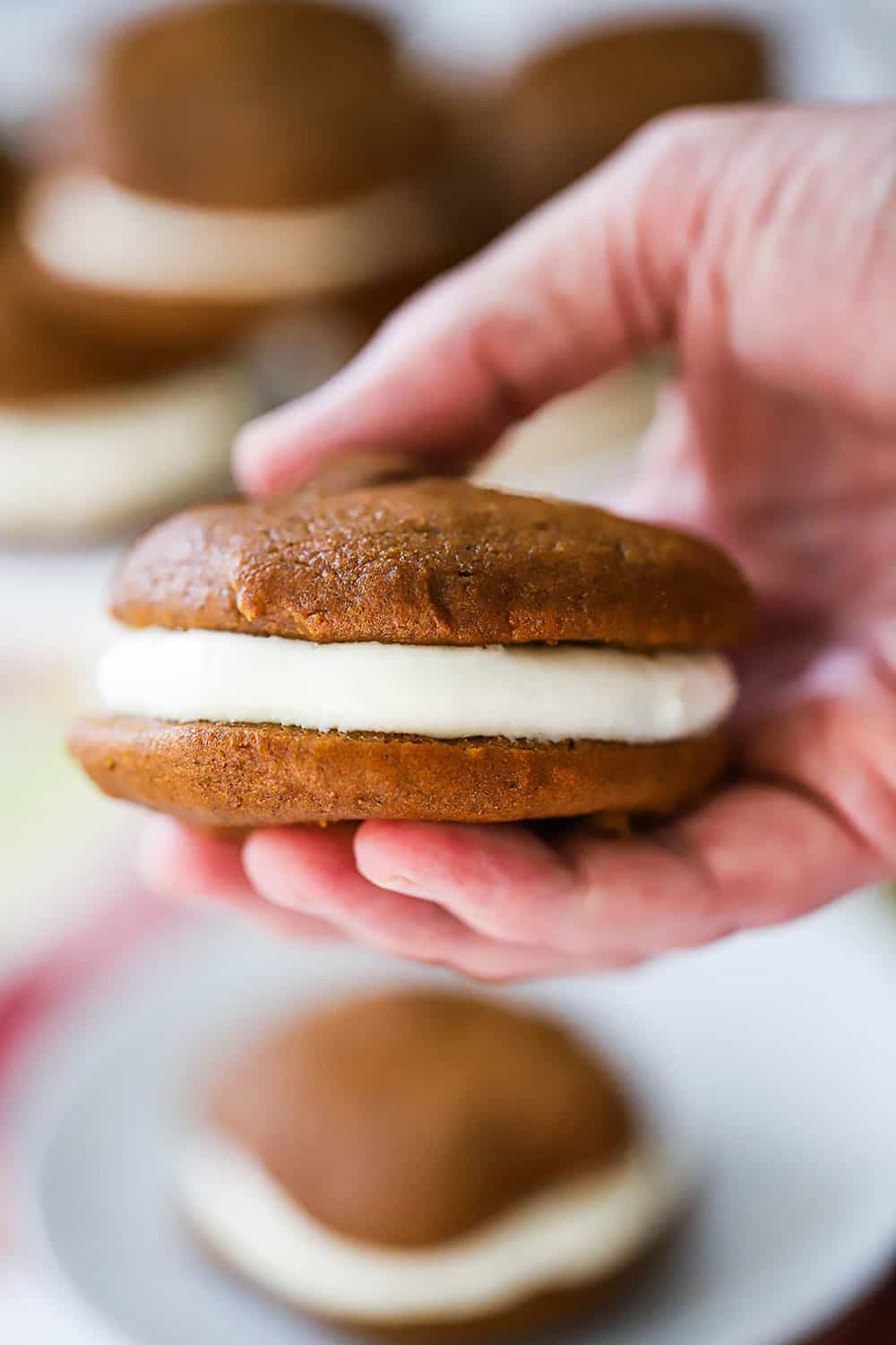 A hand holding a pumpkin whoopi pie filled with cream cheese filling.