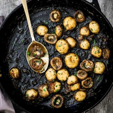 A large cast-iron skillet filled with sautéed mushrooms that have been sprinkled with fresh chopped parsley.