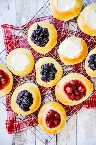 A rack that is covered with fruit-filled and cream cheese-filled Kolaches all on top of a red napkin.