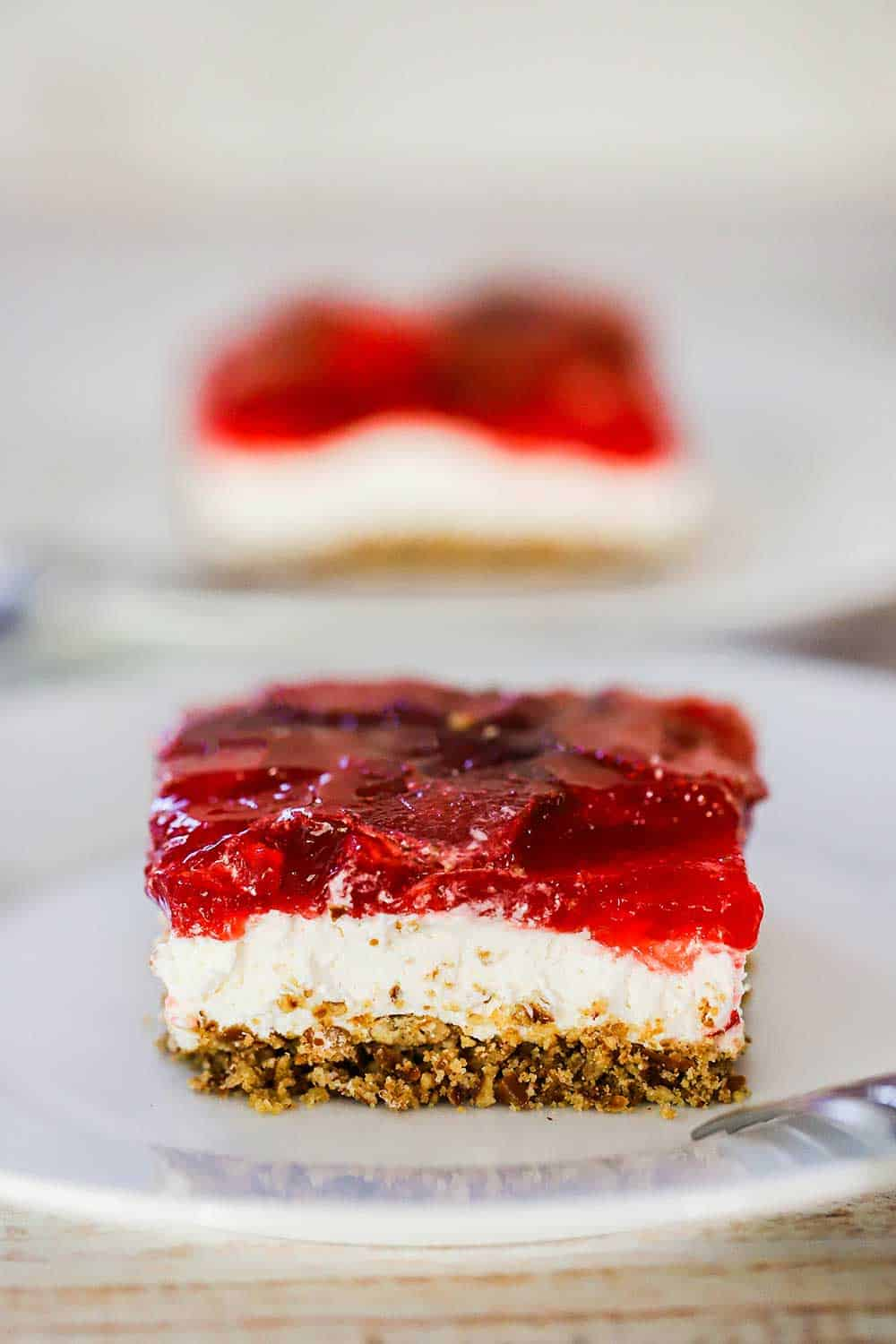 A white plate filled with a slice of strawberry pretzel salad.