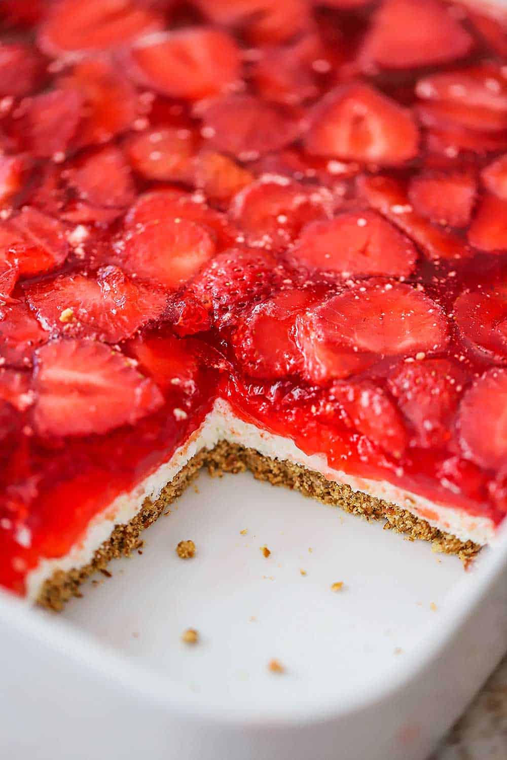 A square white casserole dish filled with strawberry pretzel salad with one piece missing in the corner.