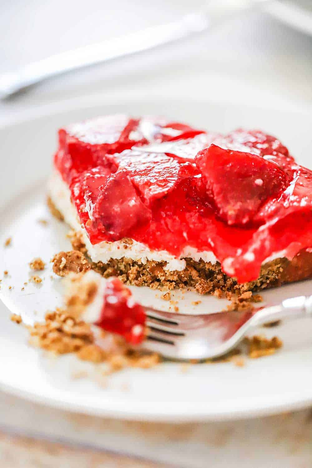 A slice of strawberry pretzel salad with a bite taken out of it sitting on a white plate with a fork next to it.