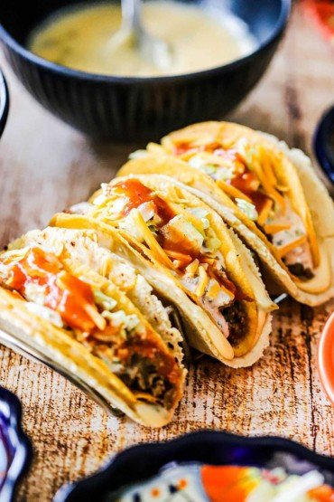Three cheesy gordita crunch tacos sitting on a taco holder on a wooden surface.