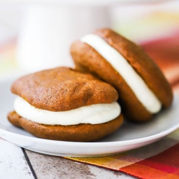 Two pumpkin whoopie pies sitting on a white dessert plate.