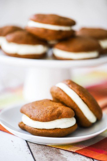 A white dessert plate holding two pumpkin whoopie pies in front of a cake platter holding more whoopie pies.